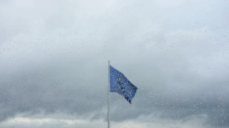 finlandês : the european flag view from behind a wet glass by rain