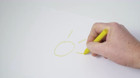 változatos : the drawing of a yellow sun with a wax crayon on a white paper Stock mozgókép