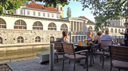 sierpien : Ljubljana, Slovenia. August 3, 2019. the sight of people in outdoor cafes along the shore of the river Ljubljanica in the city center
