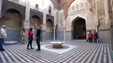 минарет : Fez, Morocco. November 9, 2019. Tourists visit the Al Attarine Madrasa courtyard.