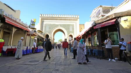 марокканский : Fez, Morocco. November 9, 2019. People walking in the Medina with the blue gate in the background