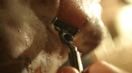 barbear : man shaving with a razor closeup Vídeos