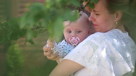 мама : Young Woman with a Baby Resting in Shady Garden on a Sunny Summer Day Стоковые видеозаписи