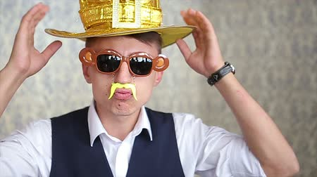 posou : Funny Guy with Hat, Glasses and Fake Mustache Posing on Light Background Slowmotion