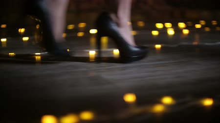 walking back : Female feet in black high heel shoes walk on the floor with blurred lights Stock Footage