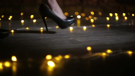 calçados : Female feet in black high heel shoes walk on the floor with blurred lights Stock Footage