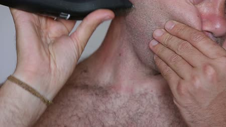 barbear : Extreme Close up of a shirtless man shaving with electric razor HD