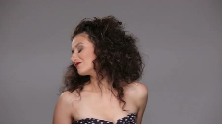 šedé vlasy : Young brunette with long brown curly hair dancing on a gray background
