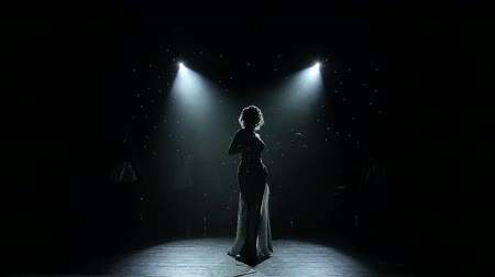 singers : Female singer backlit on smoky stage Stock Footage