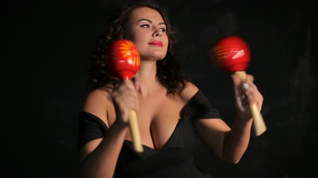 Attractive young brunette musician playing red maracas Wideo