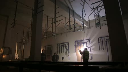 tocha : Silhouettes of workers lit by welding flashes