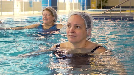rehab : Group of senior women doing aqua aerobics exercises in the swimming pool