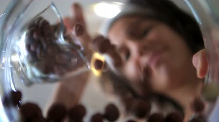 musli : Young woman scattering hazelnuts in a glass bowl