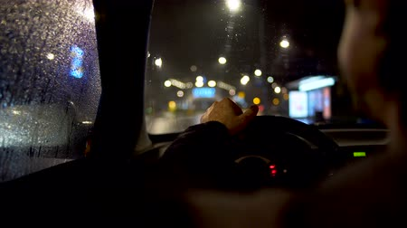 wiper : Driver eating behind steering wheel in the car parked by the city road Stock Footage