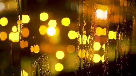nightcity : Abstract blurred night city lights and bokeh behind wet glass with raindrops Stock Footage