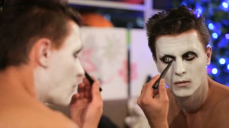 scary clown : Makeup artist at work applying halloween makeup
