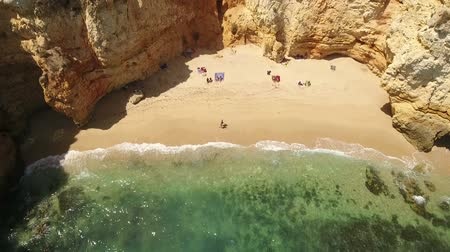 ponta da piedade : Aerial. Small beach with tourists, in the bay Ponta de Piedade. Stock Footage