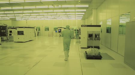 silicon : general plan engineer scientist in sterile suits, mask. are in the clean zone, takes the microchip products. Pure high-tech environment with a computer. chip fabrication