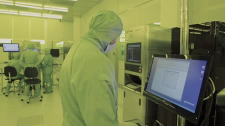 silicon : engineer scientist in sterile suits, mask. are in a clean zone looking at a process technologically advanced factory laboratory. Clean high tech environment with computer. microchip fabrication