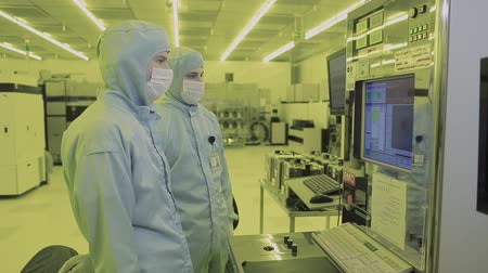 two engineer scientist in mask overalls sterile goes to the clean area. high-tech manufacturing nano technology. watching the production process