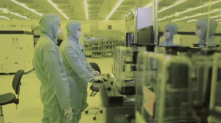 полупроводник : two engineer scientist in mask overalls sterile goes to the clean area. high-tech manufacturing nano technology. watching the production process