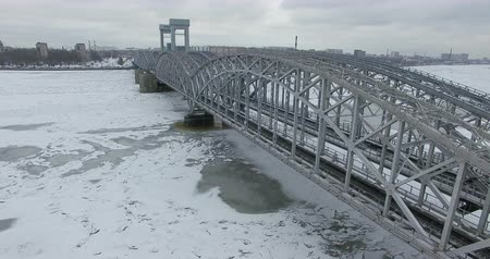 Aerial view. Flying along the river in winter overcast cold weather. Bridge over the river Petersburg. The height of the birds flight over the frozen river.