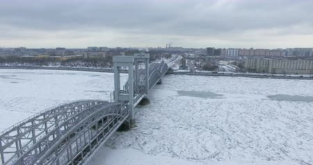 cable bridge : Aerial view. Flying along the river in winter overcast cold weather. Bridge over the river Petersburg. The height of the birds flight over the frozen river.