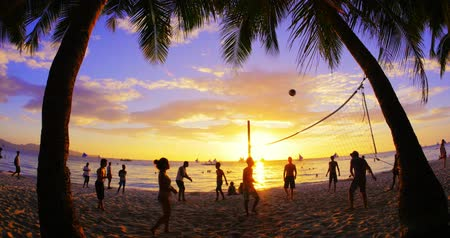 наслаждаться : volleyball players enjoy warm sunset time and play ball on tropical sandy beach. Lifestyle activity background