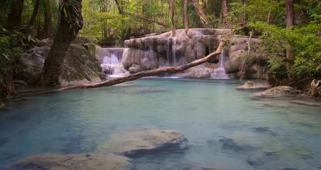 Канчанабури : Small natural pond with clear water hidden in jungle forest of Thailand. Beautiful cascades of waterfall on background. Calm and serene landscape of rainforest