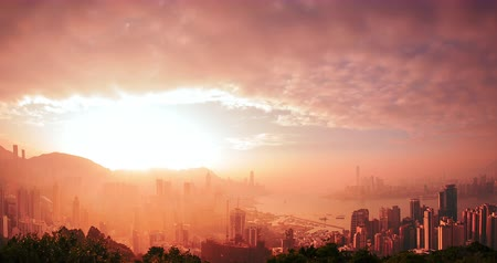 Hong Kong skyline timelapse of from day to night. Amazing panoramic view of modern city with sun light rays shining through clouds at sunset