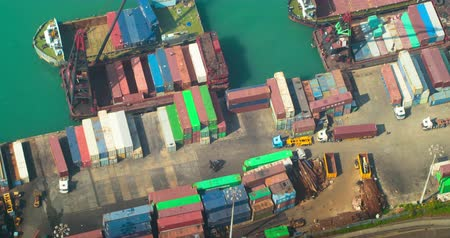 ekonomi : Aerial top view of busy activity taking place in Hongkong container terminal with crane loading goods into delivery ship and trucks moving fast. International trade Stok Video