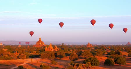 destinace : Panoramic view of Bagan historical site with many ancient Buddhist temples and hot air balloons flying over pagodas roofs. Travel destination landmarks and backgrounds