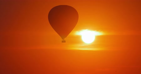 kaland : Adventure journey background. Hot air balloon flying on sunset sky with bright sun shining through clouds