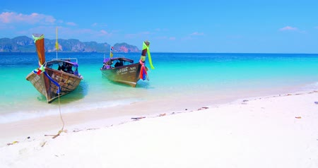 остров : Beautiful background of tropical sandy beach with two wooden thai boats on calm water of crystal clear sea in Thailand near Phuket island. Popular travel destination Стоковые видеозаписи