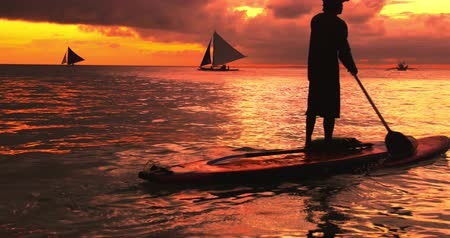 стоять : Backlit silhouette of person on paddle board at sunset. Amazing sea scape background of tropical island Boracay in Philippines Стоковые видеозаписи