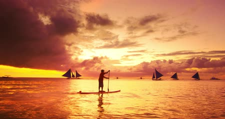remo : Beautiful sunset with dramatic clouds on orange sky, sailing boats on horizon and man moving on stand up paddle board. Boracay tropical island serene travel background