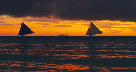 colorido : Dramatic background of two sail boats silhouettes move on late evening sea. Bright orange strip of clouds on dark sunset sky as amazing natural effect