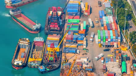 importação : Time lapse video of busy work site of container terminal in Hongkong harbor. Moving trucks and ships with cranes loading and unloading cargo for next destination