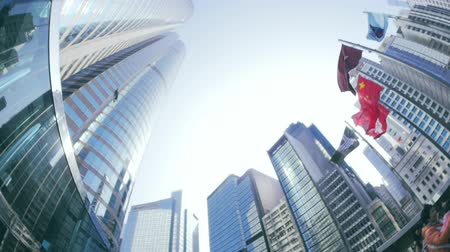 pénzügyi negyed : Waving flags on Exchange Square in Hongkong and high modern buildings around. Finance and commercial district of Asian metropolis slow motion video