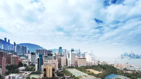 pénzügyi negyed : Panoramic cityscape of Hong Kong island. Time lapse of fast moving clouds toward camera over urban city buildings Stock mozgókép