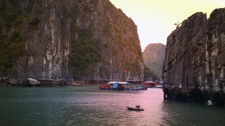öböl : Halong Bay Vietnam high definition video. Boats, mountains, cliffs and sea water at sunset