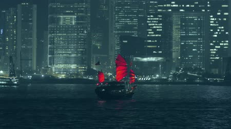 barco : Hong Kong view at night from Victoria harbor with traditional red sail junk boat and modern skyscrapers and other urban buildings of financial district of city