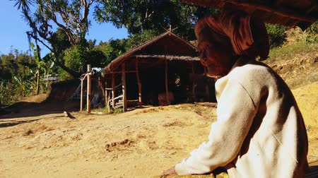 бедный : elderly Burmese woman from tribal minority sitting peacefully surrounded by traditional wooden house and local nature. Hill tribe tourist tour stopover