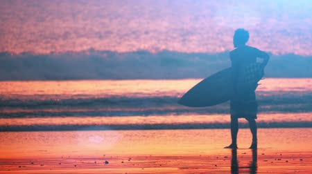 prancha de surfe : Silhouette of surfer on beach at sunset slow motion video