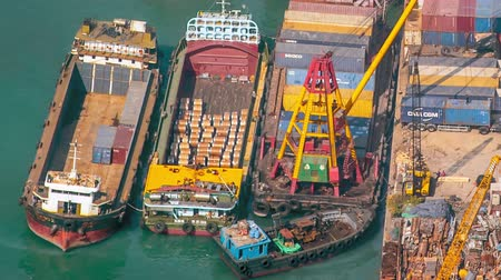 importação : Ship crane loading goods from container terminal to trade vessel of busy Hongkong container terminal