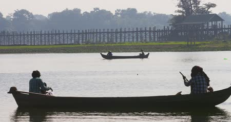 u boats : Silhouettes of fishermen on Irrawaddy river and U-Bein bridge on background. Myanmar travel destination