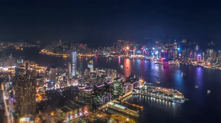 panoramic view : Aerial view of modern city at night - skyscrapers, illumination lights and boats in harbor of Hong Kong. Time lapse video