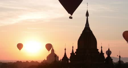 Panoramic view of Buddhist stupas and temples at sunrise with flying air balloons. Sightseeing of historical structures attracts many tourist annually