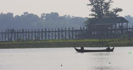 u boats : Village life in Burmese countryside of northern Myanmar. Local fishermen on wooden boat with U Bein bridge on background Stock Footage