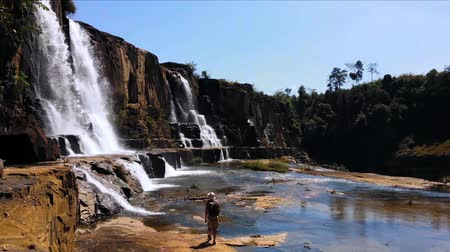 kaland : Hiker male trekking in highlands of national park. Adventure journey backpacking to Pongour waterfall in Vietnam, Dalat Stock mozgókép